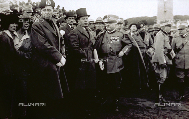 Benito Mussolini in the midst of a crowd of men, women and military in dress uniform. They seem to be waiting for a demonstration to pass