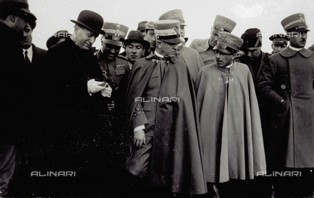 Benito Mussolini surrounded by officers in dress unifrom