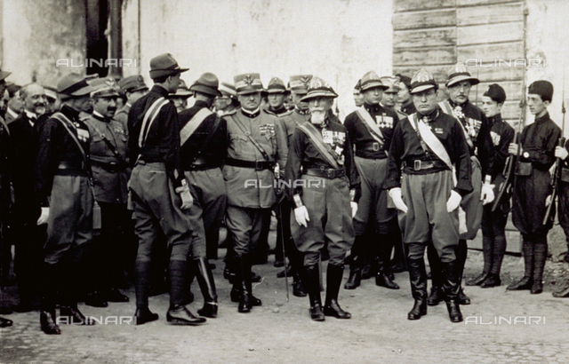 Benito Mussolini and General Emilio De Bono in alpine dress uniform. They are shown surrounded by numerous alpine troops