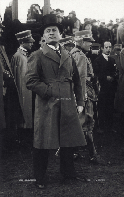 Full-length portrait of Benito Mussolini. Behind the Duce are a few officers in uniform