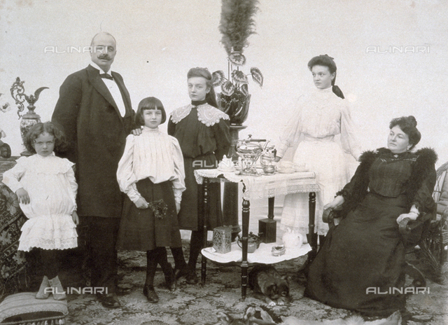 Family portrait composed of four daughters of different ages and their parents. The group is gathered around a small table on which there are various tea-pots and a complete tea service. A small dog is curled up under the table