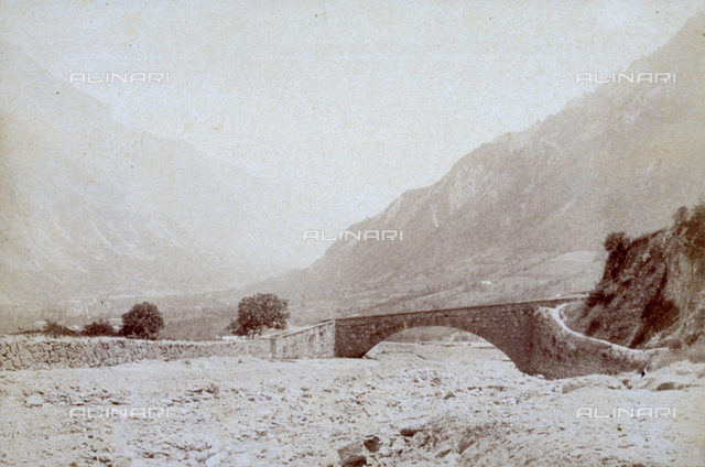 A bridge over a dry river bed. In the background a mountain landscape