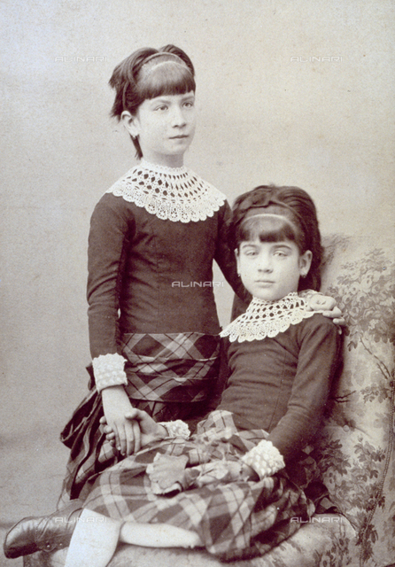 Two young sisters posing for a photograph