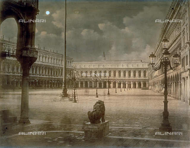 Piazza San Marco in Venice by Night. In the background of the square the Museo Correr. At the sides the Procuratie Vecchie and Nuove. In the foreground a street lamp and one of the Lions of Saint Mark seen from the right. The square is deserted and a ladder is resting against one of the street lamps in the square