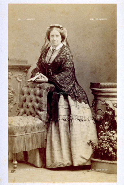 Portrait of elderly lady in day dress, with bonnet and fan. She is standing leaning on a small armchair. Beside her a small column with a book placed on top