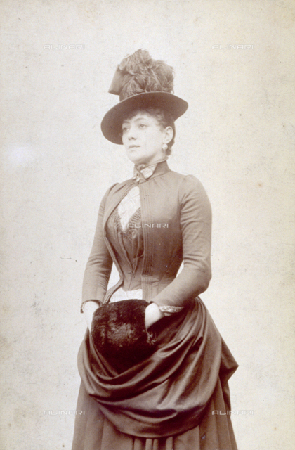 Three-quarter-length portrait of young woman in elegant clothes, with small plumed hat and muff