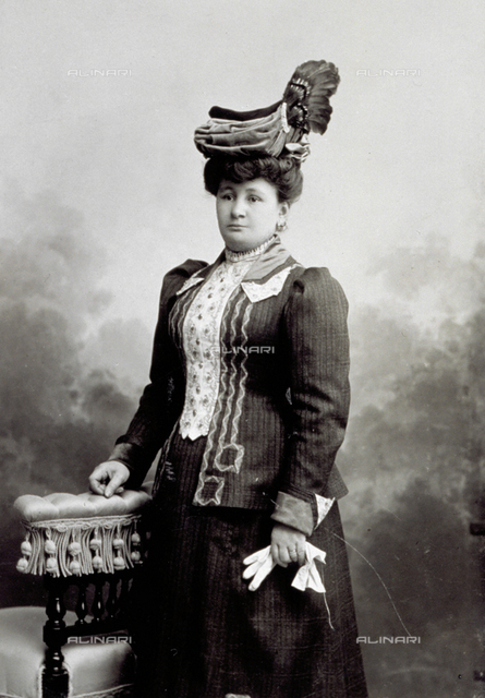 Portrait of woman in day dress: she is seen beside a seat, wearing an unusual cape with feathers and she is holding her gloves in her hands