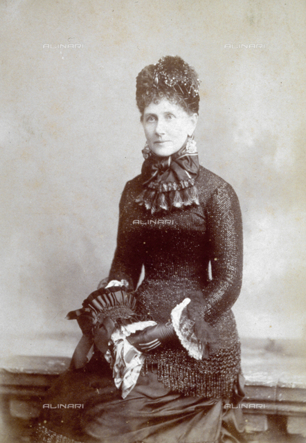 Three-quarter-length portrait of woman in elegant clothes with gloves and muff
