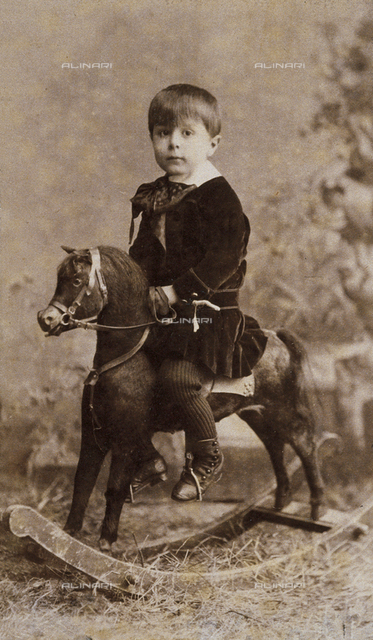 Full-length portrait of a little boy on a rocking horse