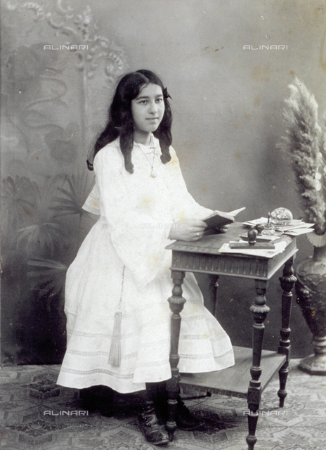 Full-length portrait of young girl sitting at a table, with a book in her hands. Some stationery can be seen on the table such as letters and a paperweight