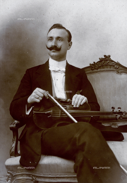 Three-quarter-length portrait, of a musician sitting on sofa, with a violin in his lap