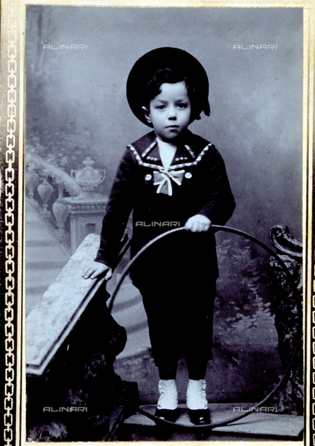 Studio portrait of a little boy dressed in sailor suit with a hoop in his hand