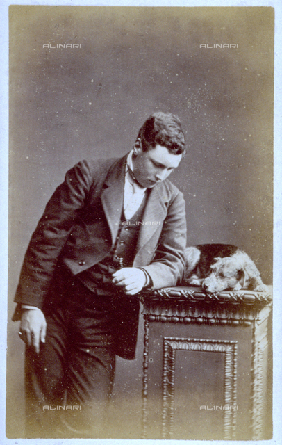 Portrait of a young man, leaning on a pillar, on which a small dog is curled up