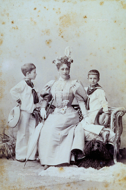 Full-length portrait of a young mother with two children in sailor outfits. The woman, elegantly dressed, is sitting on a sofa between the two children. Next to her is an umbrella, while a dog can be seen under the sofa