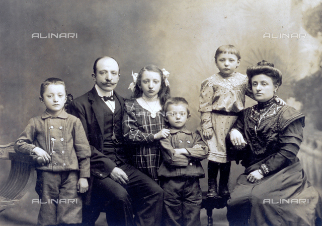 Family portrait with parents and four children, between the ages of six and ten. They are seen at three-quarter-length, wearing elegant clothes. The parents are sitting while the children are posing standing up