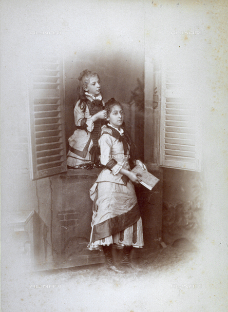 Portrait of two girls. One is looking out a window and dressing the hair of the other girl who is standing before the window holding a book