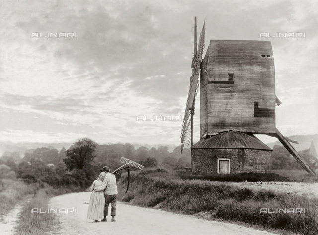 A couple of peasants arm in arm moving down a country path. A windmill can be seen on the right