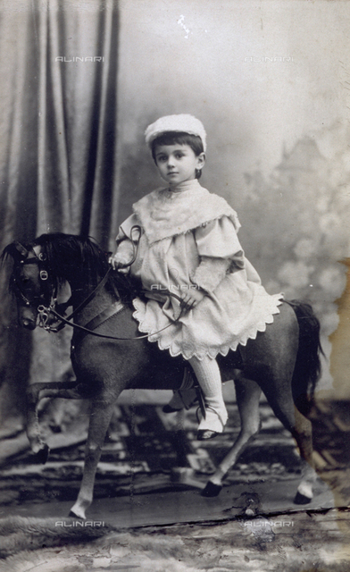Full-length portrait of a little girl on a rocking horse