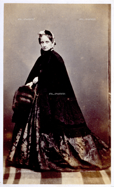 Full-length portrait of an elegantly dressed lady. She is wearing a rich damask dress and a lace trimmed shawl, fur muff and bonnet