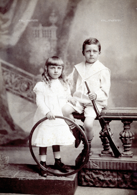 Two children, elegantly dressed, shown in front of a painted backdrop. They are holding a hoop and a toy gun