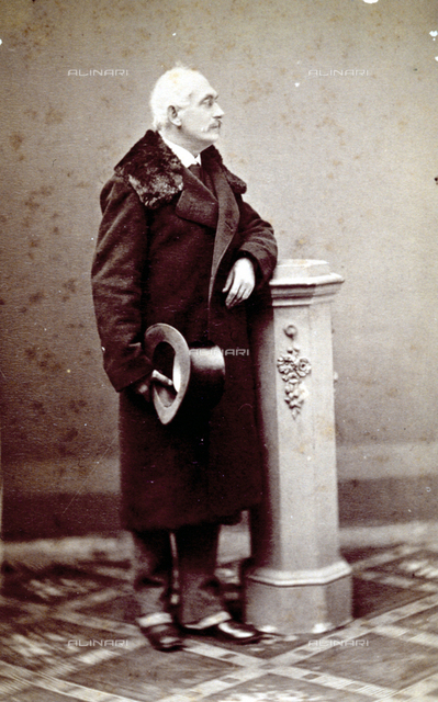 Portrait of an elderly man, standing, leaning against a column. He is wearing a coat with a fur collar and holds a top hat