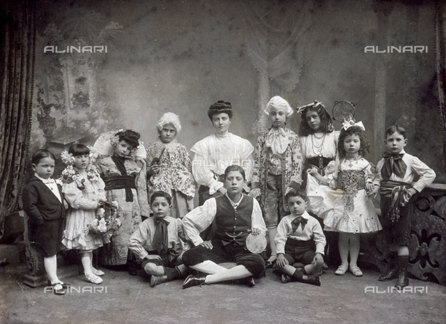 Portrait of a large group of children in costume. One girl is dressed in japanese style, others wear eighteenth century dress with wigs. Still others are dressed as musicians, with folk costumes. Three are shown seated on floor, the others standing. Behind them a painted backdrop