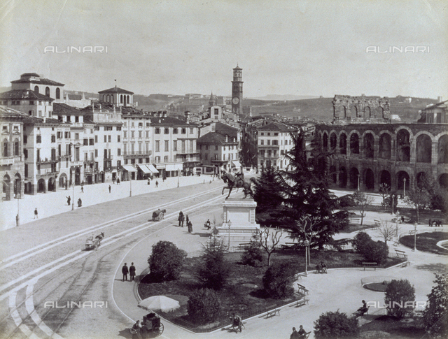 View of Piazza Bra, in Verona, with the garden and the equestrian monument to Victor Emmanuel II. On the left the 'passeggiata del Listone' and on the right the Arena. The square has people and carriages in it. In the close foreground, the cart of an itinerant vender protected by a big umbrella