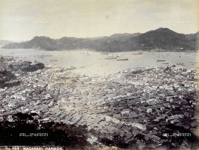 Bird's eye panorama of the city of Nagasaki, with the gulf and the harbor. Numerous ships are anchored in the harbor