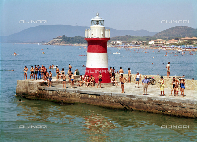 Wharf off the beach of Castiglione della Pescaia, crowded with bathers. In the foreground the lighthouse, and in the background the coast with the bathing establishments