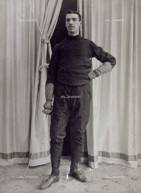 Full-length portrait of a fencer in front of a drop-curtain, holding a foil
