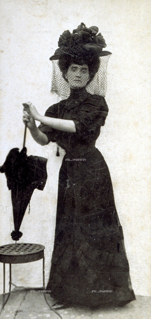 Full-length portrait of an elegantly dressed woman. She is wearing a dark high-necked dress, a large hat with veil and is leaning on an umbrella