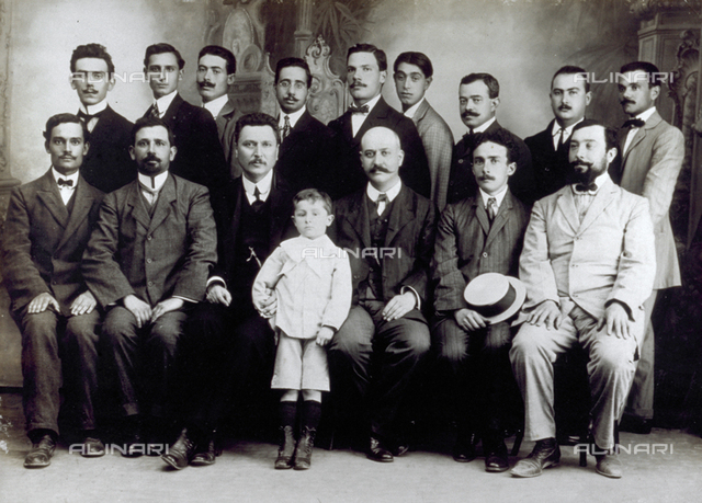 Full-length portrait of a group of men and a child