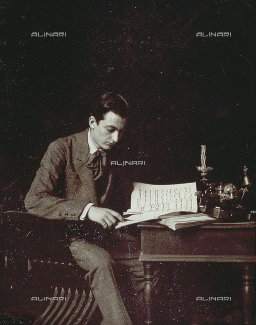 Portrait of a young man seated at a table reading some music scores. On the table is a violin