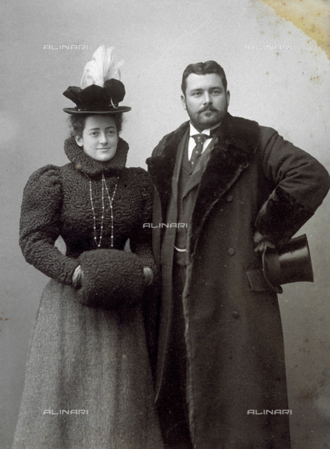 Full-length portrait of a young elegantly dressed couple. He is wearing a coat with a fur collar and holding a top hat. She is wearing a fur bolero, a hat with feathers, and a fur muff