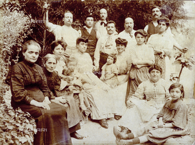 Large family group in a garden. Included are an elderly lady, a few children, a small dog
