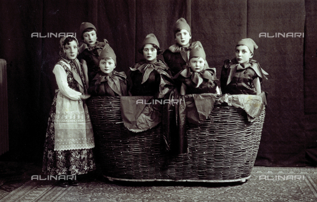 Portrait of a group of children in fancy dress costume. Six children are dressed as strawberries and are inside an enormous basket. The little girl standing, outside of the basket, is dressed as a russian woman