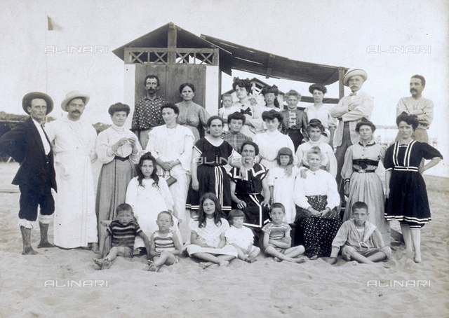 Group of men, women and children on a beach. Behind them a cabin. They are all wearing bathing costumes