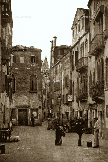 View of the Salizzada San Samuele in Venice, with passersby. On the right a fruitvender and further back the sign of a municipal school. In the background a lane