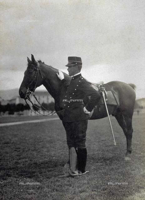 Portrait of a soldier in uniform, standing next to his horse