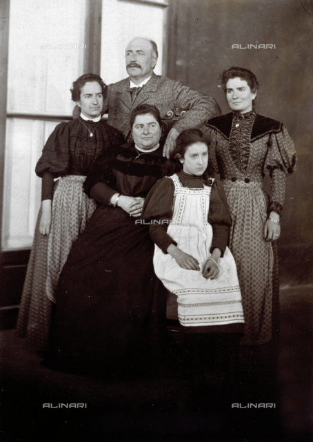 Full-length portriat of a family group composed of a man, three women and a girl. The women wear dark dresses with velvet inserts and bouffant sleeves. The girl is wearing a white smock over a dark dress