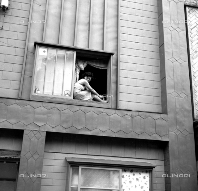 Young girl portrait at the window of a traditional Japanese house