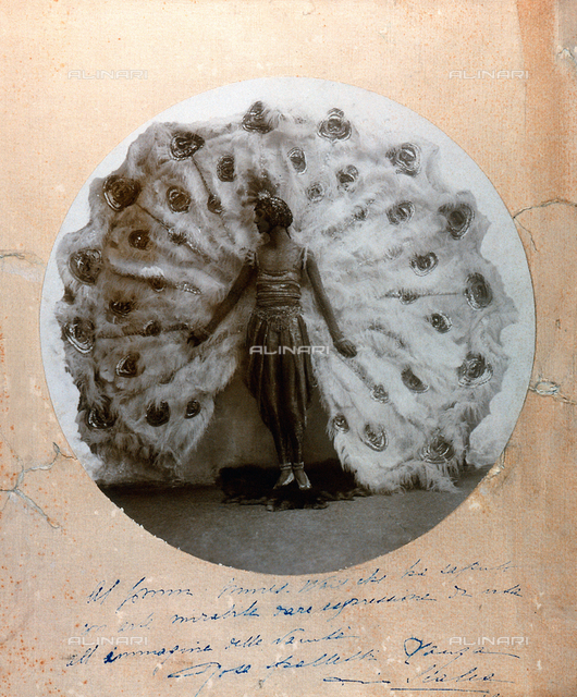 Round portrait of Countess Rosa Spalletti Lanza Scalea, wearing a dress decorated with sequins and paillettes. She poses in front of a large fan made of feathers and embroidered inserts, which imitates the tail of a peacock