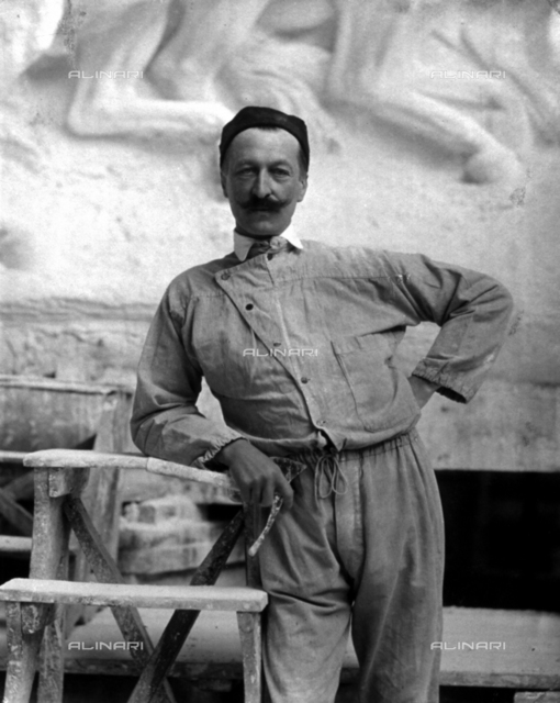Portrait of the famous sculptor Pietro Canonica in work clothes. The artist is posing in his studio holding a tool of his trade in his right hand