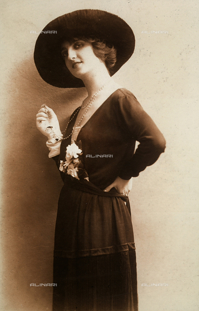 Profile portrait of a young woman, wearing a wide-brimmed hat and a dress decorated with a few gardenias. In her gloved hand she holds on to a chain with pearls