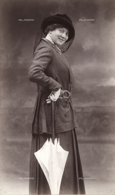 Full-length portrait of a smiling woman. She is wearing a striped skirt and jacket and a hat with a veil. In her gloved right hand, she holds an umbrella