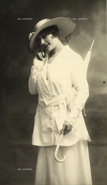 Full-length portrait of a young woman wearing a jacket and a wide-brimmed straw hat with a flower and veil. Under her arm she carries a parasol.