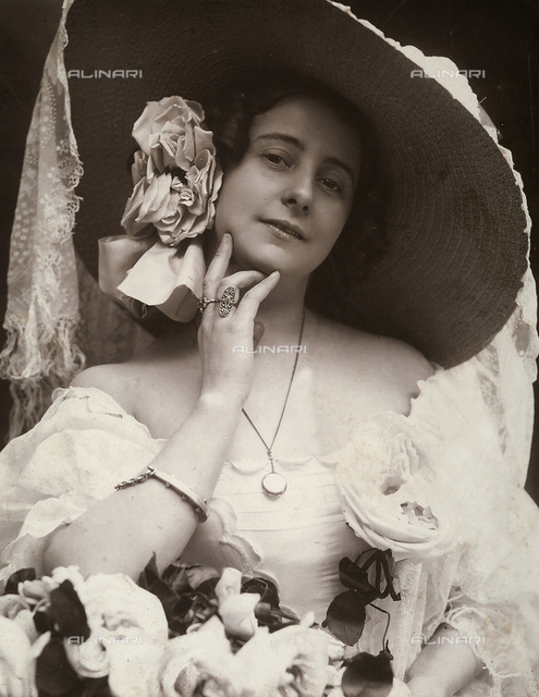 A young woman in a low-cut, embroidered summer dress. She has a cloth flower in her hair and wears a large straw hat with an ebroidered vail