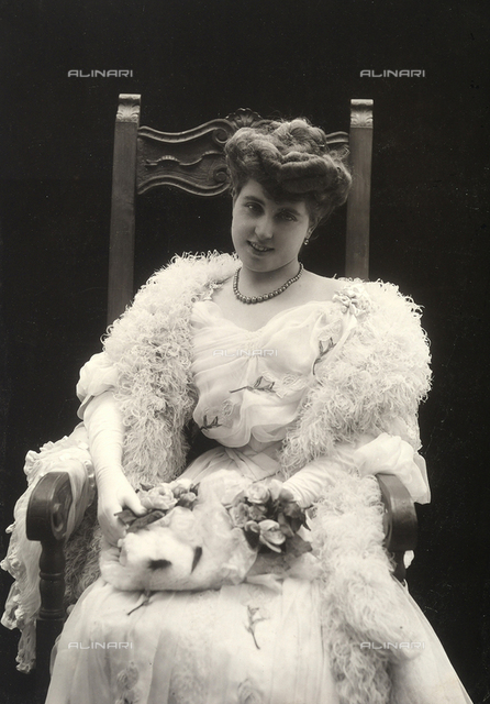 Portrait of young, smiling woman, seated in a chair. She is wearing an evening gown with lace accents in the form of roses; on her shoulders, a feather boa and in her hands a muff of ermine fur