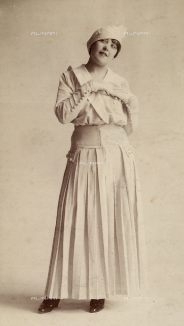 Full-length portrait of a young woman wearing a light-colored summer dress, gloves and a hat