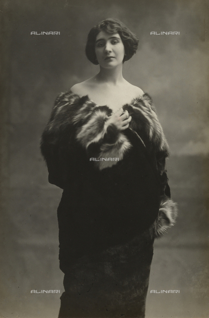 Full-length portrait of a young woman wearing a beaver fur coat over her bare shoulders. The collar and cuffs of the coat are in pole-cat fur